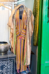 "An antique dealer displays an old palestinian dress using the multi-colored Damascene ""Joseph"" fabric - by Aaron Cederberg"