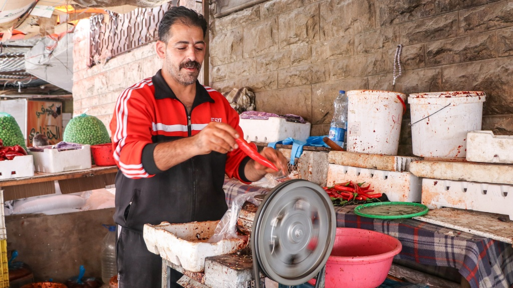 A man grinds red peppers in the Syrian Market in Ramtha - by Stephanie Saldaña