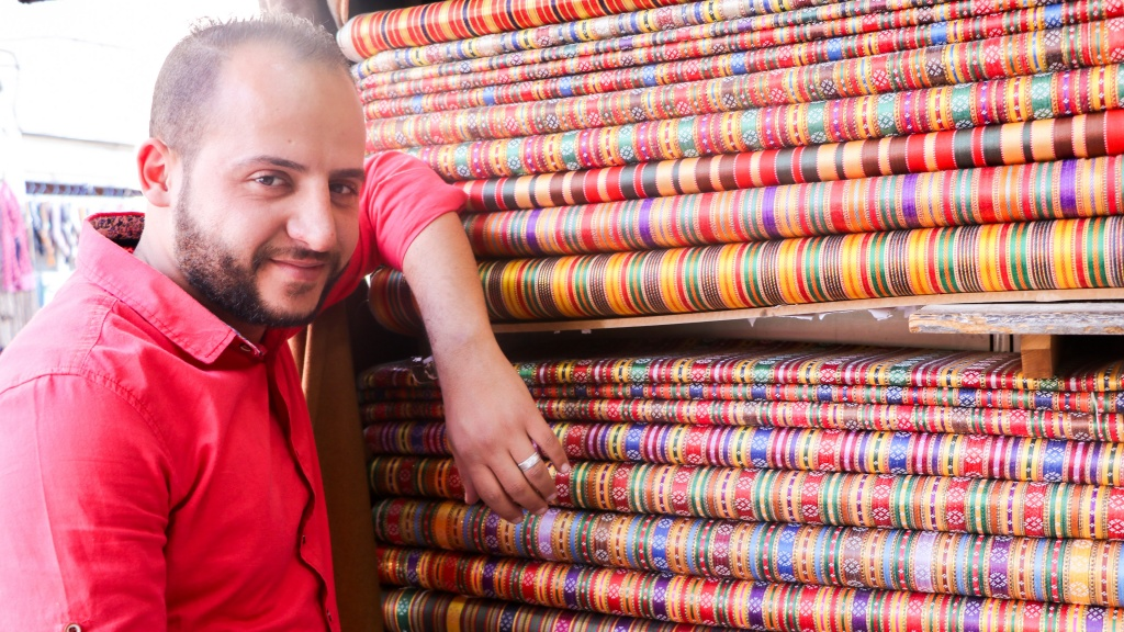 Mahmoud al-Shoukre poses next to the fabric he used for his wedding clothes - by Stephanie Saldaña
